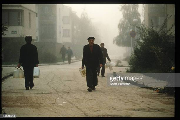 Unidentified individuals collect water September 12 1995 in Sarajevo Bosnia and Herzegovina When Bosnia declared its independence in March 1992 a...