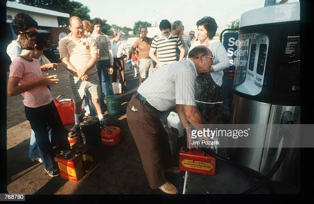 Unidentified individuals line up with cans to buy gas at a Mobil gas station July 1979 in Suffolk County NY In 1977 oil prices went up to more than...