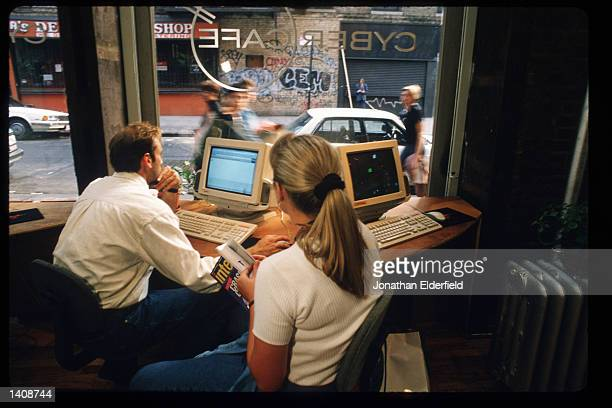 Unidentified individuals use a computer at Cyber Cafe September 22 1995 in New York City The cafe allows customers to drink coffee while surfing the...