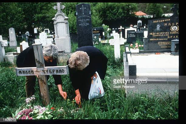 Unidentified individuals visit a grave May 14, 1996 in Bosnia and Herzegovina. Slobodan Milosevic instituted Serbian nationalism, encouraged ethnic...