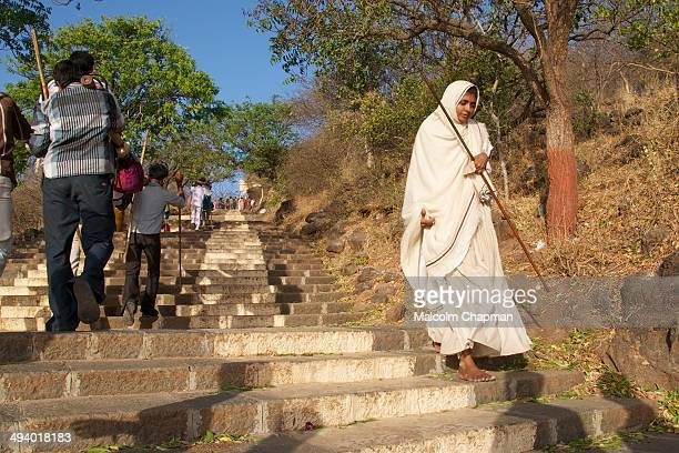 Unidentified Jain nun walking down Mount Shatrunjaya near Palitana Gujarat India With 863 temples the hill is sacred to Jains