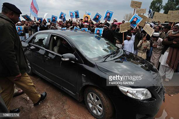 Unidentified lawyers drive into the Adiyala prison during a protest by Shabab-e-Islami Pakistan activists in Rawalpindi on February 14 in the support...