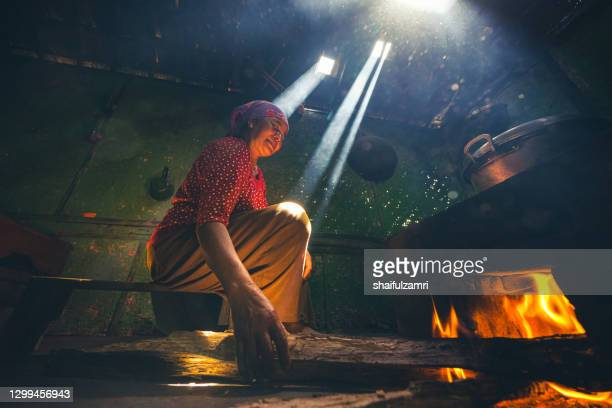 unidentified local lady preparing a lunch for family with traditional   wood kitchen in cemoro lawang village of bromo - shaifulzamri foto e immagini stock