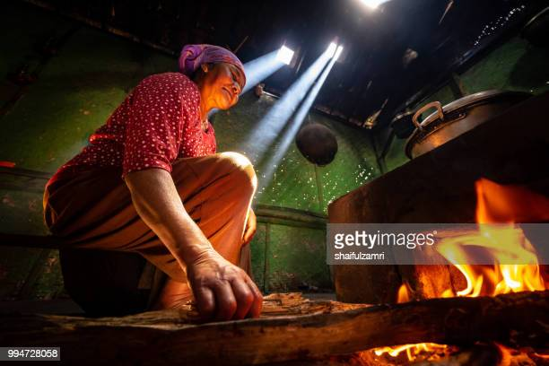 Unidentified local lady preparing a lunch for family with traditional wood kitchen in Cemoro Lawang village of Bromo, East Java, Indonesia.
