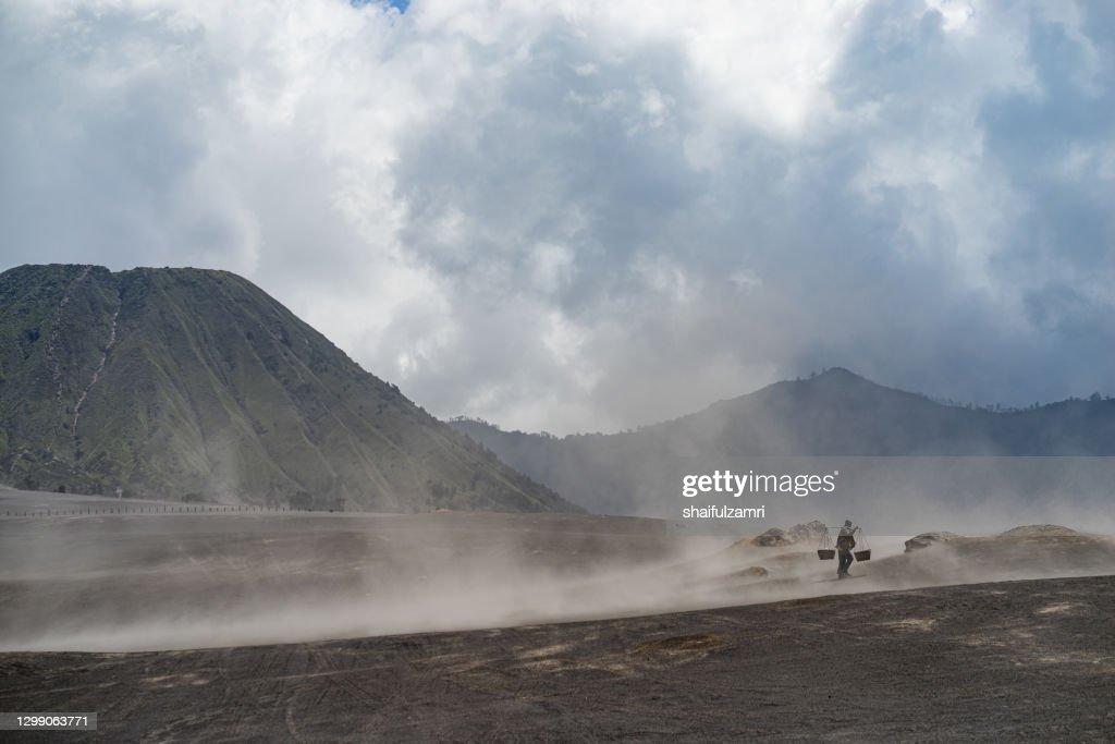 Unidentified local people of Tengger walking in sandstorm  at savanna of Tengger caldera, Mt. Bromo : Stock Photo