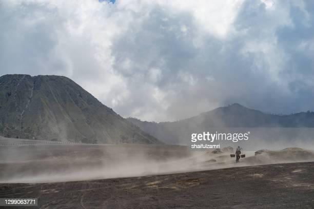 unidentified local people of tengger walking in sandstorm  at savanna of tengger caldera, mt. bromo - shaifulzamri bildbanksfoton och bilder