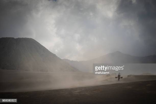 unidentified local people of tengger walking in sandstorm at savanna of tengger caldera, mt. bromo, east java of indonesia. - shaifulzamri foto e immagini stock