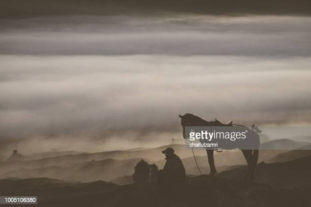 unidentified local people or bromo horseman at the mountainside of mount bromo with noise and dual tone effects. - shaifulzamri stock pictures, royalty-free photos & images