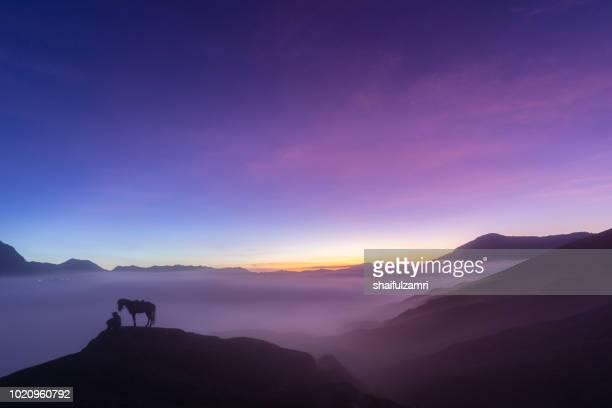 unidentified local people or bromo horseman at the mountainside of mount bromo, semeru, tengger national park, east java of indonesia. - mt bromo stock pictures, royalty-free photos & images