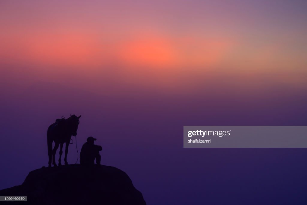 Unidentified local people or Bromo Horseman pause a while with his horse  at the mountainside of Mount Bromo : Stock Photo