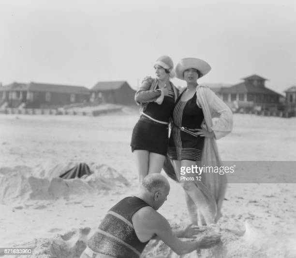Unidentified man building sand castle and two women Long Beach New York 1910 by Arnold Genthe 18691942 photographer