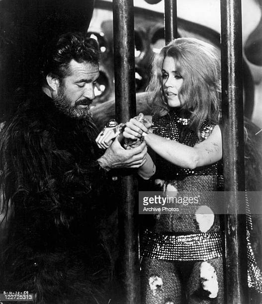 Unidentified man holding Jane Fonda's hands as she's tied to a cage in a scene from the film 'Barbarella', 1968.