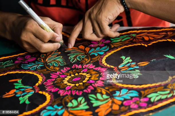 "unidentified man is making the traditional moon kite or locally known as ""wau bulan"" at kelantan, malaysia - malaysian culture stock pictures, royalty-free photos & images"