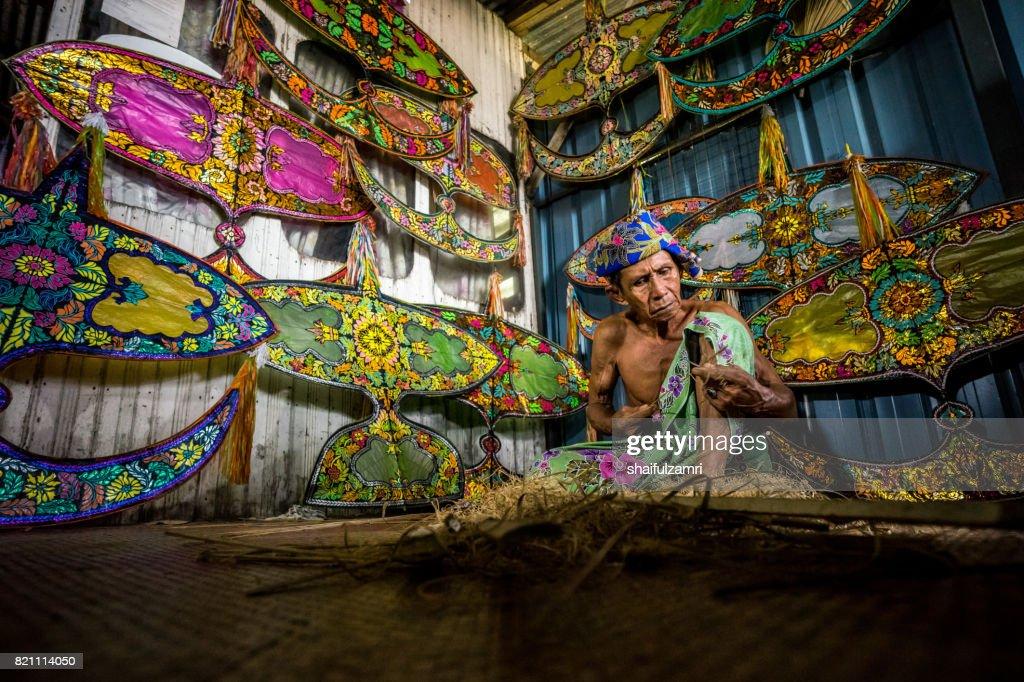 "Unidentified man is making the traditional moon kite or locally known as ""Wau Bulan"" in Kelantan : Stock Photo"