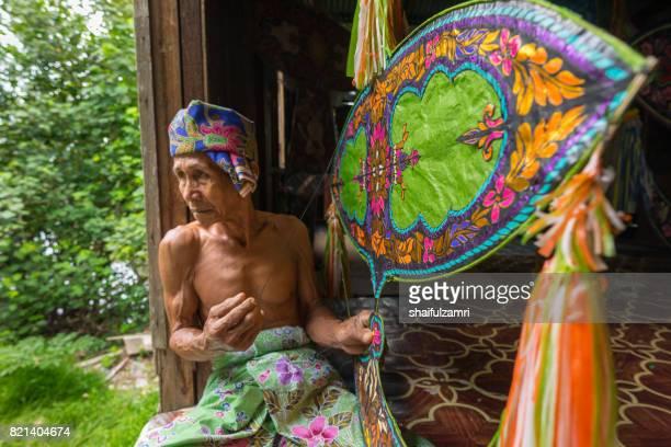 "unidentified man is making the traditional moon kite or locally known as ""wau bulan"" at kelantan, malaysia. - shaifulzamri foto e immagini stock"