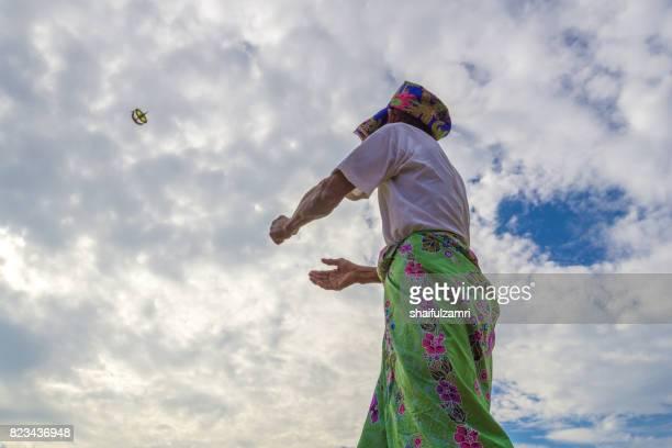 "unidentified man is playing the traditional moon kite or locally known as ""wau bulan"" in kelantan, malaysia. - shaifulzamri fotografías e imágenes de stock"