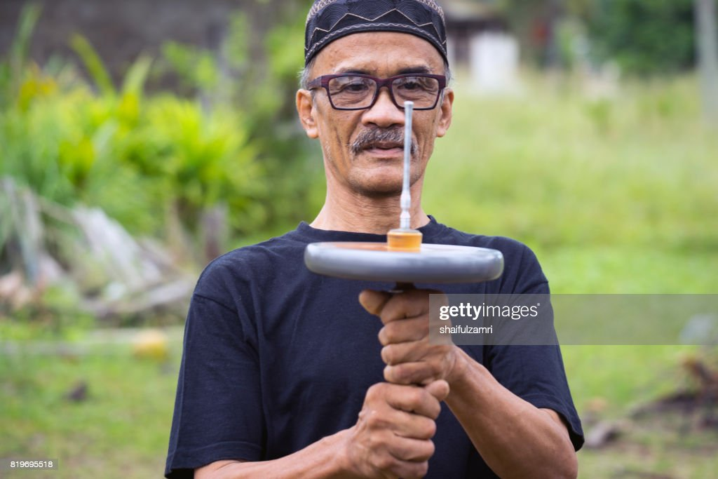 """Unidentified man playing """"Gasing"""" or tops spinning, is a traditional games popular among Malay in Malaysia. : Stock Photo"""