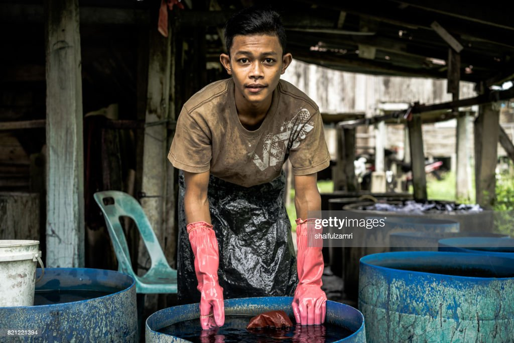 Unidentified man wash a Batik after colouring process : Stock Photo