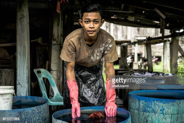 unidentified man wash a batik after colouring process - shaifulzamri foto e immagini stock