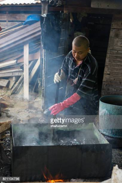 unidentified man wash a batik in boiled water - shaifulzamri photos et images de collection