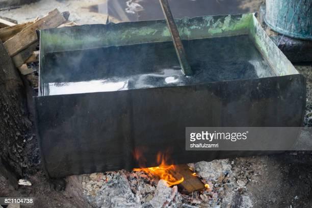 unidentified man wash a batik in boiled water - shaifulzamri stockfoto's en -beelden