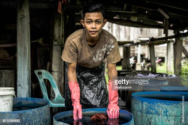 unidentified man wash a batik in the traditional process of making batik kelantan. - shaifulzamri foto e immagini stock