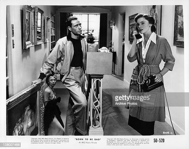 Unidentified man watches Joan Leslie on the phone in a scene from the film 'Born To Be Bad' 1950