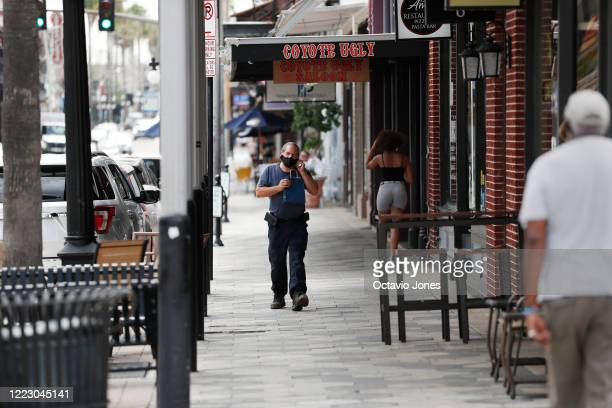 Unidentified man wearing a mask walks on 7th Avenue in the Ybor City neighborhood on June 26, 2020 in Tampa, Florida. Florida surpasses previous...