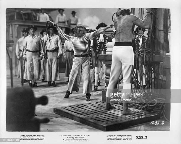 Unidentified man whips another in a scene from the film 'Against All Flags' 1952