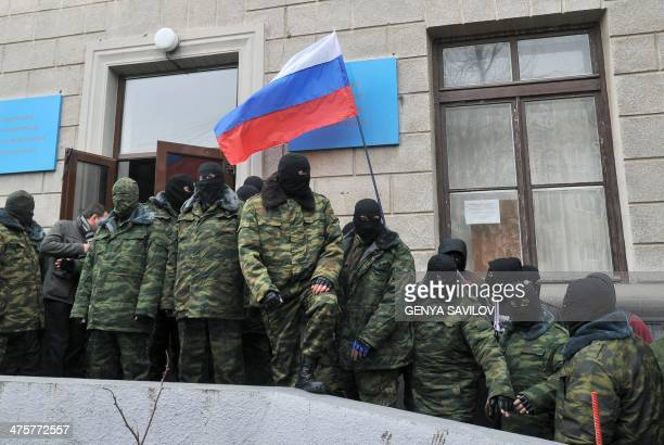 Unidentified masked individuals hold a Russian flag as they block the Trade Union building in Simferopol the administrative center of Crimea on March...