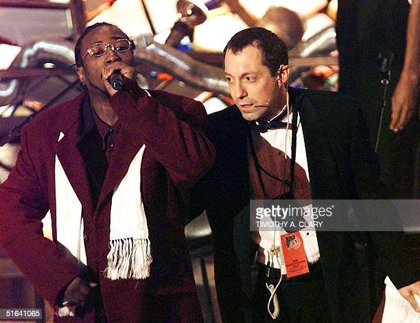A unidentified member of the group Wu Tang Clan is taken off the stage after jumping on the stage and taking the microphone as the Grammy was about...