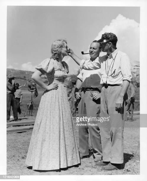 Unidentified men adjust Virginia Bruce's glasses offcamera from the film 'Bad Man Of Brimstone' 1937