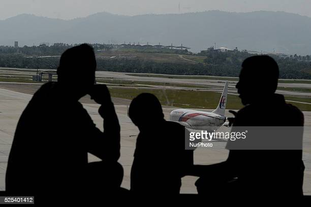 Unidentified men chats while watching Malaysia Airlines a plane taxied on the tarmac of Kuala Lumpur International Airport as it enters the second...