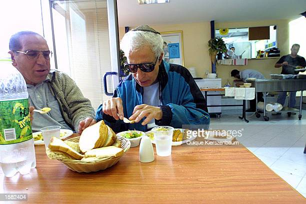 Unidentified men eat a hot meal at the Meir Panim soup kitchen October 31 2002 in Jerusalem Israel Approximately 400 people eat at the soup kitchen...