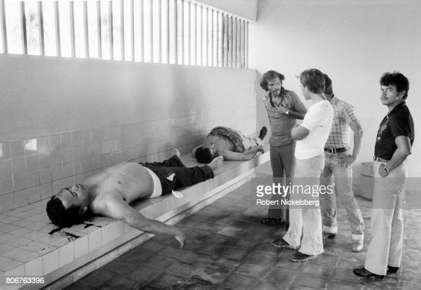 Unidentified men look at one of two corpses in the city morgue in San Salvador El Salvador August 10 1984 Both victims were shot in the face and...