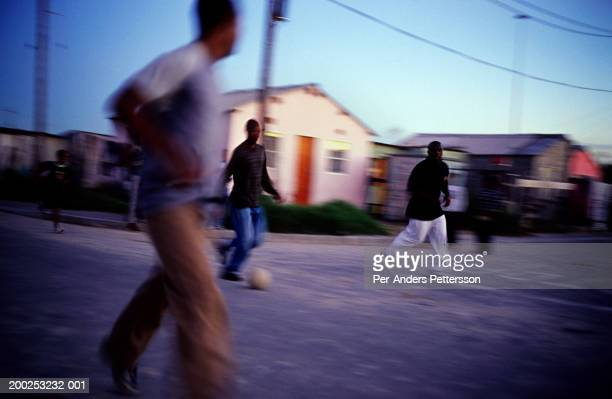 Unidentified men play soccer in the streets on October 1 2004 in Khayelitsha the biggest black township outside Cape Town South Africa It's estimated...