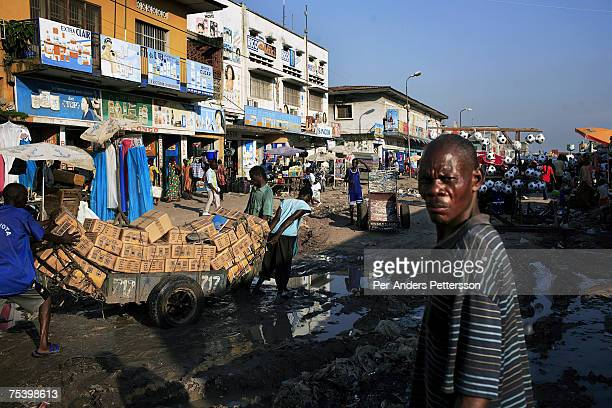 Unidentified men push a cart with goods on a muddy road leading the central market on May 4 2006 in central Kinshasa Congo DRC The area one of the...