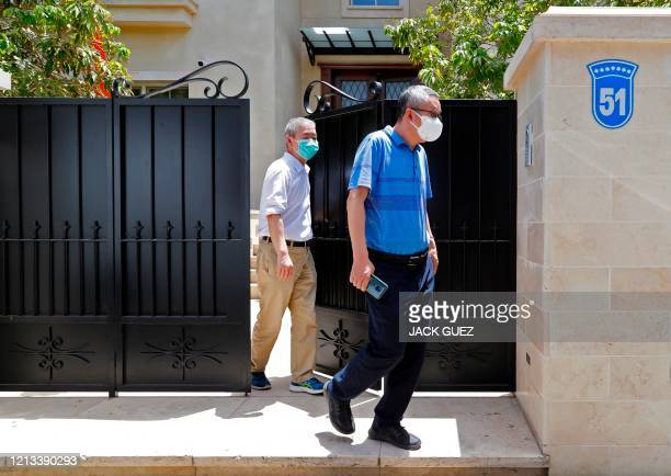 Unidentified men walk out of the residence of Israel's Chinese ambassador on the outskirts of Tel Aviv after he was found dead on May 17, 2020. - The...