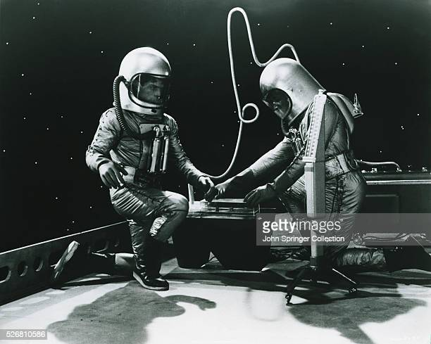 Unidentified movie still of two astronauts examining their equipment. Undated photograph.