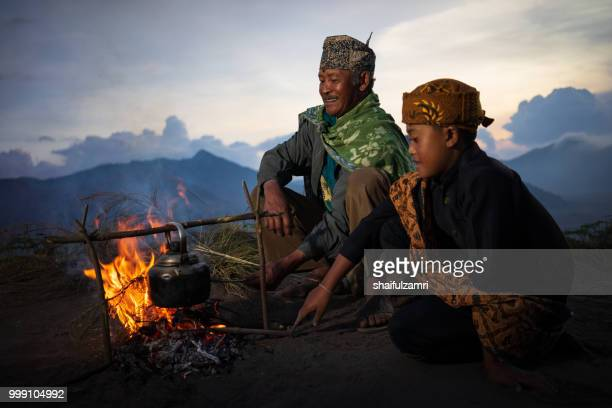 unidentified old man pose for camera with his grandchild at cemoro lawang village, east java. most of people in here still practising a traditional way of life. - bromo tengger semeru national park stock photos and pictures