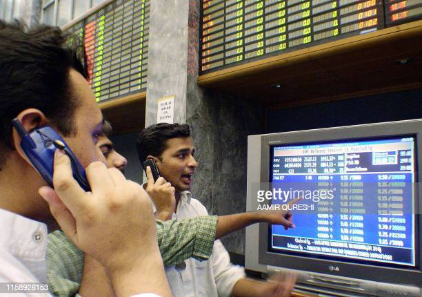 Unidentified Pakistan retail investors trade using their mobile telephones as they watch a monitor at the main trading hall of The Stock Exchange...