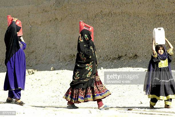 Unidentified Pakistani women and a young girl carry water containers on their heads as they make their way towards their homes after filling the...