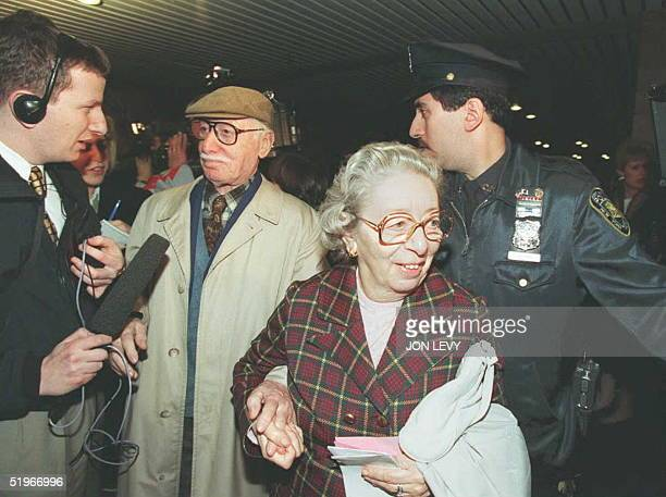 Unidentified passengers from the Queen Elizabeth 2 are rushed past the media by a New York City police officer after they disembarked following their...