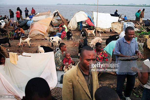 Unidentified passengers travel on a boat made of big trees on the Congo River on June 29 2006 outside Mbandaka Congo DRC The boat traveled with about...