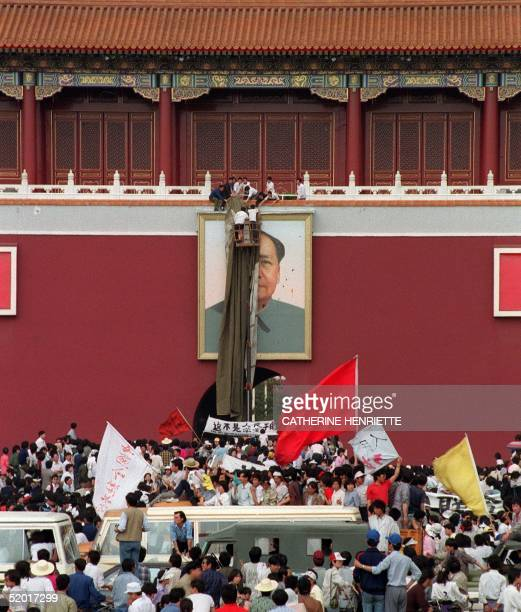 Unidentified people cover a portrait of China's Communist founding father Mao Zedong with a khaki canvas after it was defaced with a trail of blue...