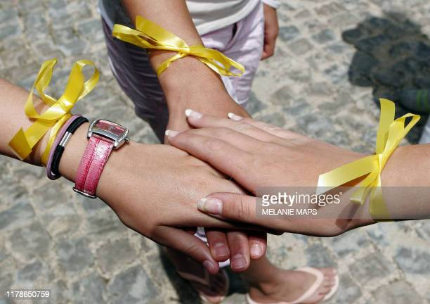 Unidentified people join their hands together as they wear a yellow ribbon outside the reception of the Ocean Club in Praia da Luz Portugal 12 May...