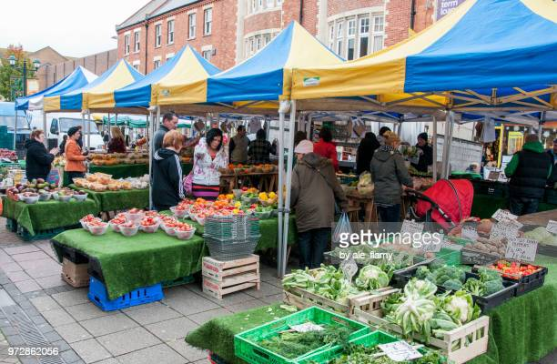 bournemouth, uk - november 17, 2012: unidentified people shop for fruits and vegetables at farmers market in bournemouth - farmers market stock pictures, royalty-free photos & images