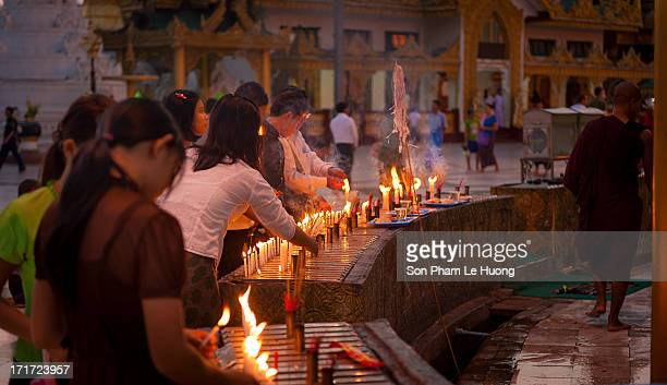 Unidentified peoples praying with the burned candles in Shwedagon pagoda at dawn.