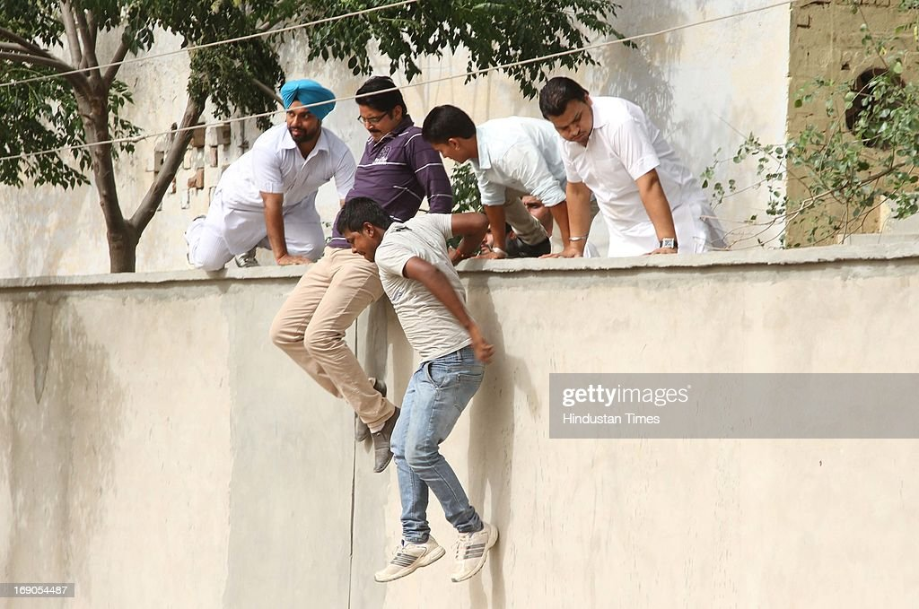 Unidentified person who allegedly tried to capture booths at village Maan in Mukatsar fleeing from school campus under the cover of police to escape by scaling boundary wall on May 19, 2013 in Bathinda, India. Elections were held today for district level. Several people and policemen were injured after clashes broke out between the workers of the ruling Akali Dal and the opposition Congress following alleged booth capturing by the Akali workers.