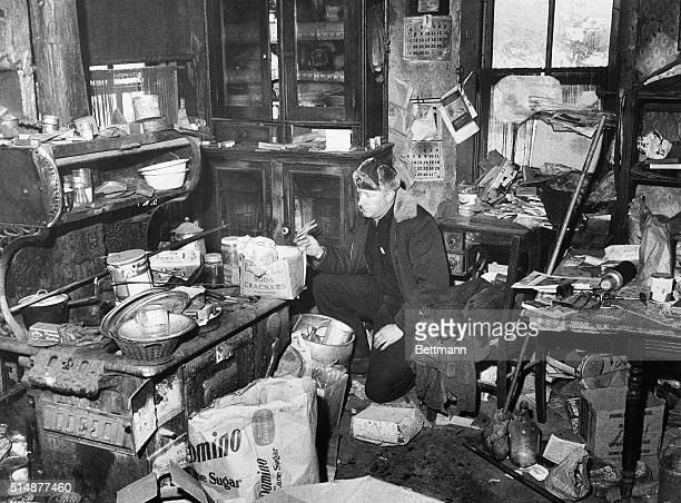Unidentified police officer examines the junk-littered kitchen in the farm home of Edward Gein, where authorities found human skulls and other parts...